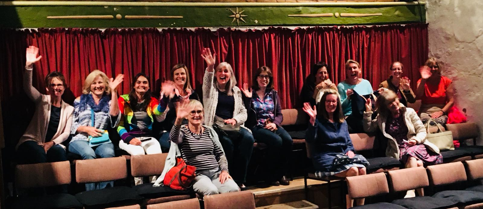 women in theatre waving